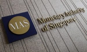 Front of grey, stone building with Monetary Authority of Singapore logo in gold-colored lettering