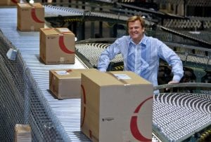 Overstock.com CEO Patrick Byrne standing in an overstock warehouse with cardboard boxes