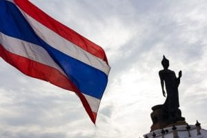 flag of thailand with buddhist statue in background