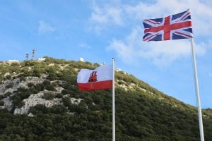 UK and Gibraltar flags waving in wind with small mountain in background