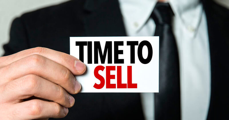 man holding a card printed with time to sell