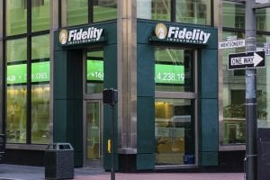 Corner of a building with glass windows on a busy New York City street with Fidelity Investments signs and a one way stret sign pointing to the right.