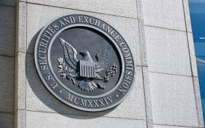 Metallic emblem and seal of the U.S. Securities and Exchange Commission outside of a stone building