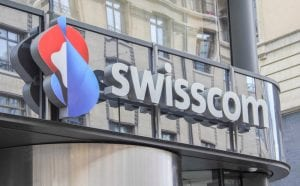 Front of large building with reflective windows in Switzerland with Swisscom logo in front