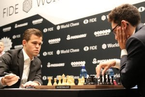 Two men wearing suits playing chess with lots of people watching at the World Chess Championship.