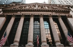 Front of the New York Stock Exchange showing large pillars and three American flags