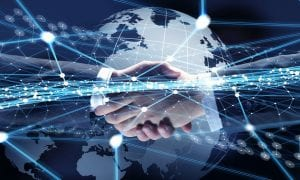 Two business men shaking hands with globe and technological matrix in background