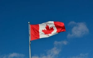 Canadian flag waving in the wind with blue skies in the background