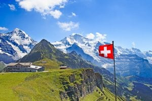 Swiss flag, red with white cross, with grassy mountains in the foreground and snow capped mountains in the background.