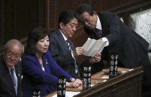 Japan Prime Minister Shinzō Abe sitting in Japanese parliament meeting with two men and one woman, all wearing business formal attire.