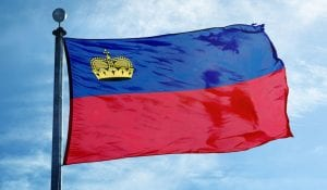 Liechtenstein flag (red and blue) waving in the wind with a sunny blue sky in the background.
