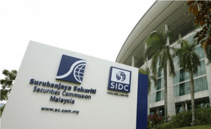 "White sign outside building with many glass window that reads: ""Securities Commission Malaysia"" in blue lettering"