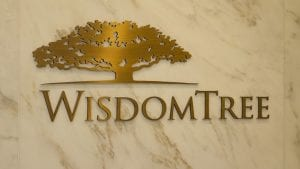 WisdomTree Investments gold company logo inside of a building on a marble wall