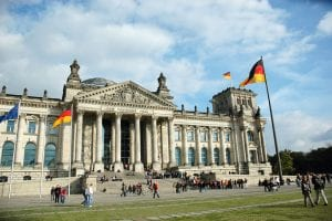 Germany flags and the front of a large historic building with blue sky in the background