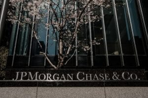 Front of JPMorgan Chase & Co building with tree in background and JPMorgan sign in foreground