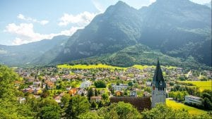 A country view of Liechtenstein with houses, vintage buildings, a church steeple, and mountains in the background.