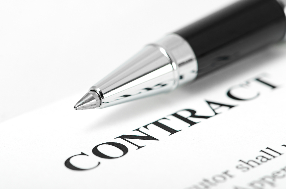 Picture of a contract paper with a ball pen placed on top of the paper.