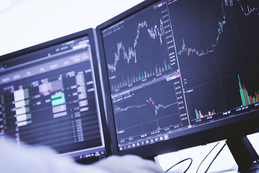 Picture of a trader sitting in front of a dual monitor configuration