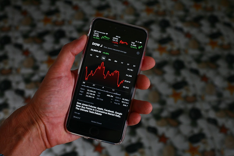 Picture of a hand holding the smartphone with trading app running